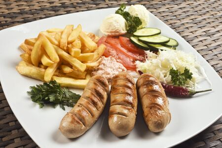 Fast food meat meal with German sausage, french fries and mixed vegetable garnish. 写真素材 - 133121807