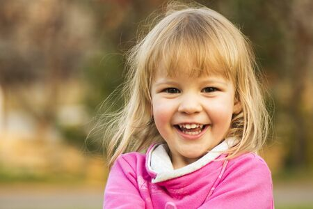Child portrait of cheerful laughing cute blond hair little girl, happy childhood concept.