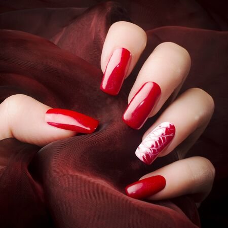Female hand with beautiful red nails on red background, nail care and manicure concept.