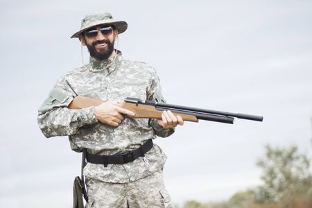 Portrait of smiling hunter or army soldier in military uniform with rifle in nature.