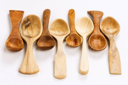 Different unique wooden spoons on white background, kitchen equipment, wood carving concept.