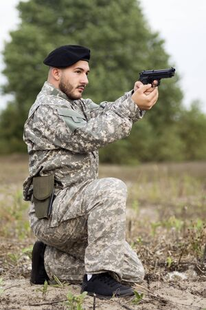 The army soldier in military uniform is holding pistol and aiming outdoors in nature.