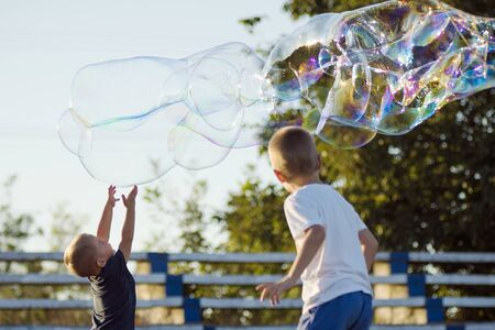 The little boys are playing with giant colorful soap bubbles outdoors, happy childhood and active life concept.