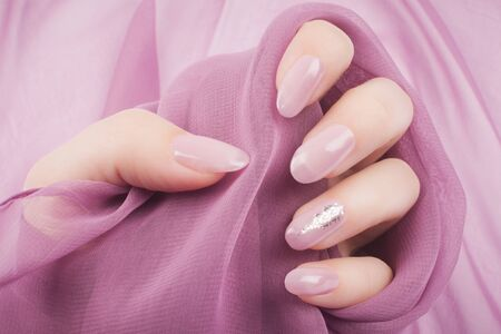 Female hand with beautiful shiny bright rose decorated nails is on bright rose background, nail care and manicure concept.