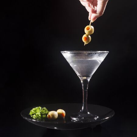 Martini cocktail drink with olives on black background.