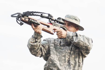 The army soldier or hunter in military uniform is aiming and shooting with crossbow weapon on white background. 스톡 콘텐츠