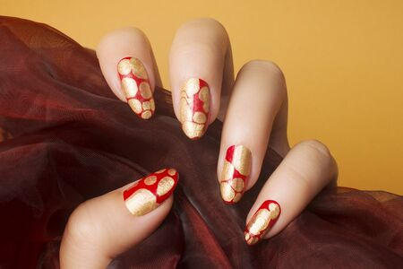 Female hand with red gold nails on orange background, nail care and manicure concept. 스톡 콘텐츠