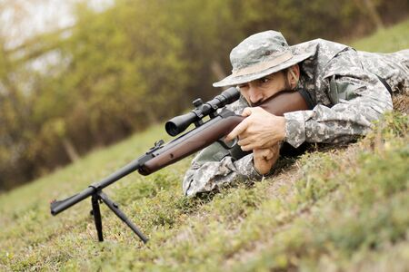 The army soldier or hunter in military uniform is aiming and shooting with sniper rifle weapon lying down on grass.