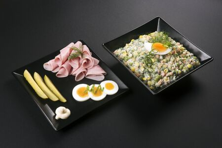 Gourmet appetizer from ham, eggs, pickle and french salad or russian salad served in black plates on black table in elegant restaurant.