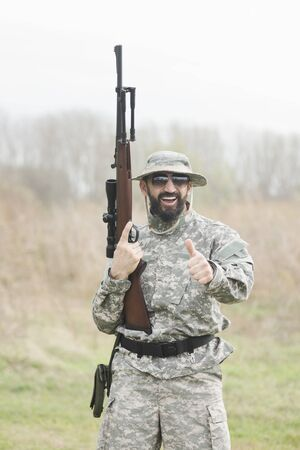 The smiling hunter or military person with gun or rifle is showing thumb up outdoors. 스톡 콘텐츠