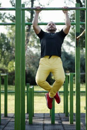 The young athlete is doing pullups street workout training outdoors in the park.