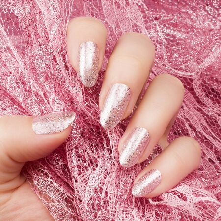 Female hand with glittered shiny rose nails is holding a glittered rose lace, nail care and manicure concept.