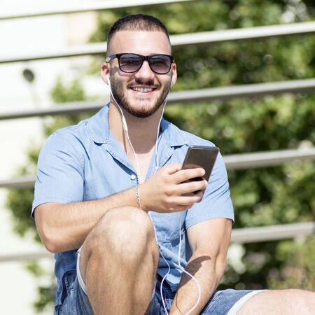 The smiling young guy with earphones is using phone for listening music outdoors.