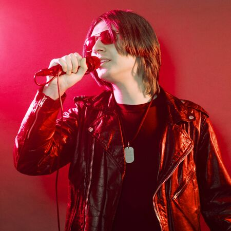 The young guy in black leather jacket is singing rock music on red illuminated stage.