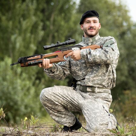 The smiling soldier in military uniform is holding a crossbow weapon outdoors. 스톡 콘텐츠