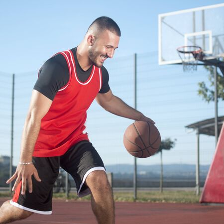 The smiling young basketball player is playing basketball on playground outdoors, streetbasket or streetball concept. Stock fotó