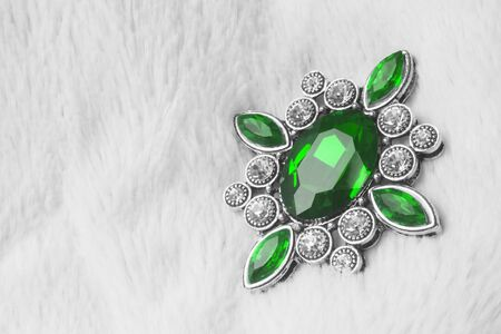 Beautiful luxurious brooch jewel or jewelry with green gem or smaragd on white fur background. Banque d'images - 135351718