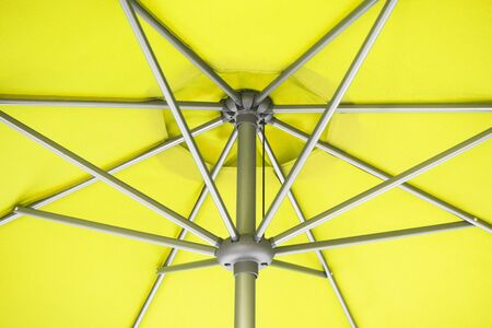 Close-up and geometric star shapes of yellow parasol or under umbrella.