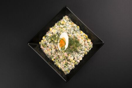 Decorated French salad or Russian salad is served in black plate on black background.