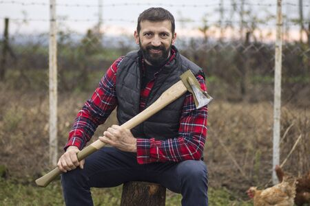 Portrait of smiling lumberjack or woodcutter with axe, country life concept.