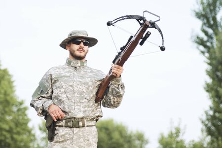 The hunter or army soldier in military uniform is holding a crossbow weapon outdoors.