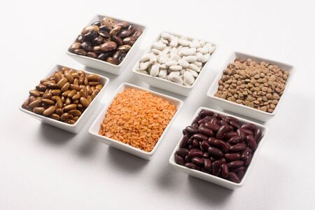 Group of different legumes, beans and lentils in white dishes on white background.