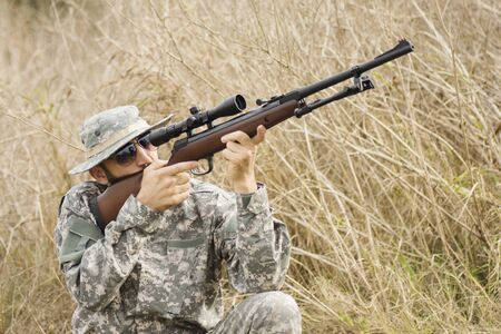 The hiding hunter in military uniform is aiming with shotgun or air gun outdoors in nature.