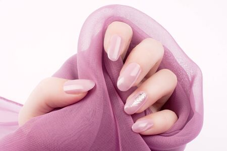 Female hand with shiny pink rose nails is holding a pink decoration on white background, nail care and manicure concept. 스톡 콘텐츠