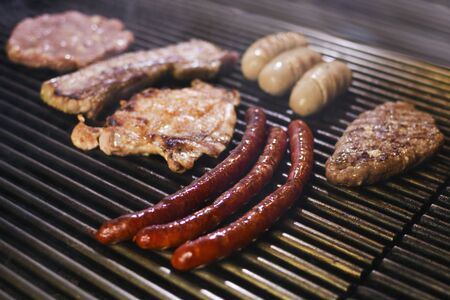 Different grilled barbecue meats, sausages, hamburger and chicken are baking on the grill. 스톡 콘텐츠