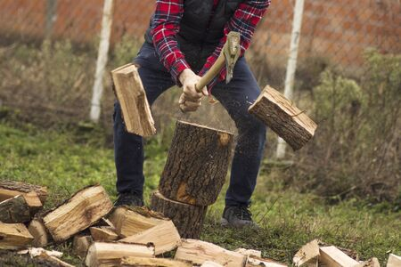 The lumberjack or woodcutter is cutting wood or firewood with axe outdoors.