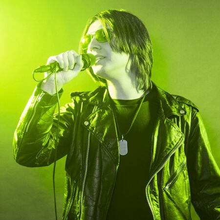 The young guy in black leather jacket is singing rock music on green yellow illuminated stage.