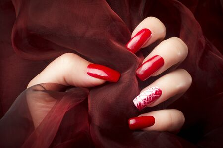 Female hand with beautiful red nails on red background, nail care and manicure concept. Stock Photo