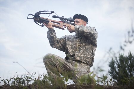 The army soldier in military uniform is aiming with crossbow weapon outdoors.
