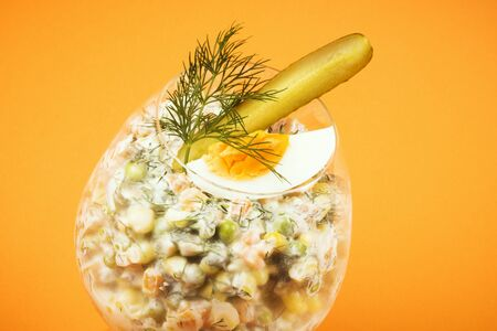 Decorated Russian salad with egg, pickle and dill is in drinking glass on orange background. 스톡 콘텐츠