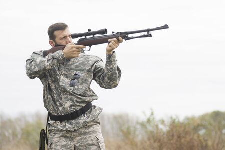 The hunter in military uniform is aiming and shooting a weapon outdoors, hunting sport.