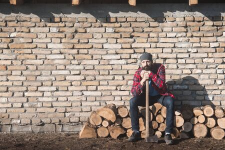 The sad and tired lumberjack worker with axe is sitting on firewood on brick wall. 스톡 콘텐츠