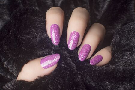 Female hand with glittered pink nails is holding black fur, manicure and nail care concept. 스톡 콘텐츠