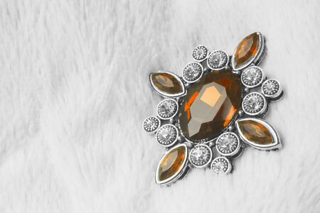 Beautiful luxurious brooch jewel or jewelry with brown gem or topaz on white fur background. 스톡 콘텐츠