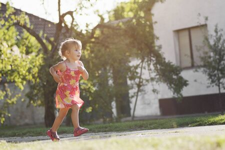 The playful cute little girl in dress is running on the street outdoors.