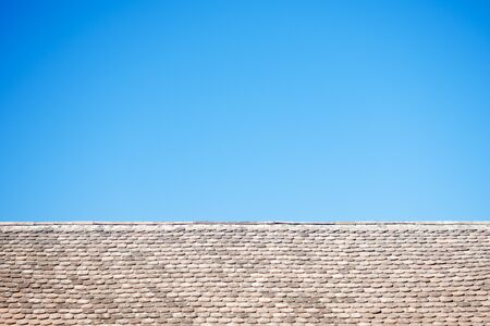 Old tiles on roof and flat blue sky background.