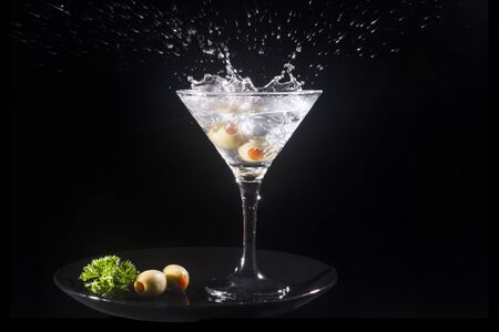 Splashing martini cocktail drink with green olives is on black background.
