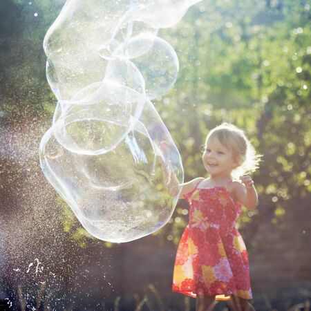 The cute little girl in dress is playing with giant soap bubbles outdoors. Foto de archivo