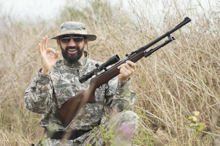 The smiling hunter in military uniform with rifle is showing OK with his hand outdoors.