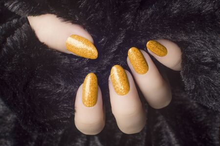 Female hand with glittered orange nails is holding black fur, manicure and nail care concept.