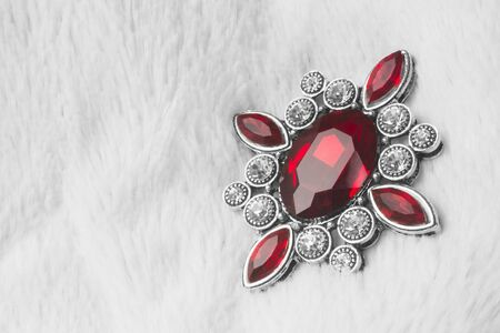 Beautiful luxurious brooch jewel or jewelry with ruby red gemstone on white fur background.