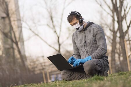 The man with protective mask and protective gloves is using laptop out of office outdoors in the park.