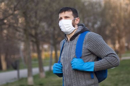 The man with protective mask and protective gloves is outdoors in the park.