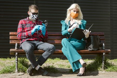 People`s life in season of coronavirus, man and woman with protective mask and gloves are sitting on bench outdoors.