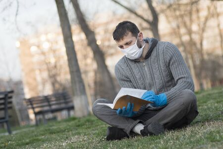 The man with protective mask and protective gloves is reading a book outdoors in the park. Foto de archivo
