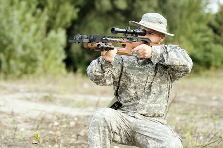 The hunter or soldier in military uniform is aiming and shooting with crossbow weapon.